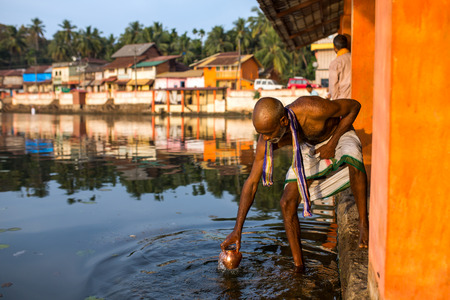 vedas: Gokarna, India - January 16, 2016: Unidentified temple brahmin taking water for puja from sacred lake in Gokarna. The city is a holy pilgrimage site for Hinduists