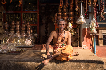 vedas: Gokarna, India - January 16, 2016: Unidentified temple brahmin sitting in his shop in Gokarna. The city is a holy pilgrimage site for Hinduists Editorial