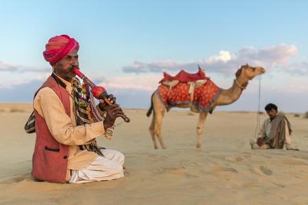 thar: Jaisalmer, India - March 13, 2016: Unidentified man play traditional music after camel ride in Thar desert near Jaisalmer, India. Editorial