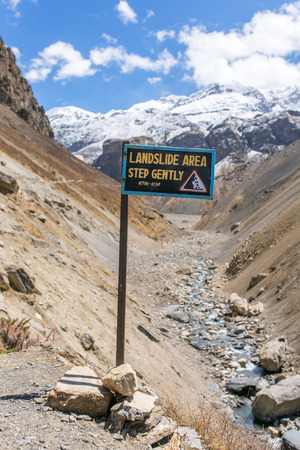 trip hazard sign: Landslide prone area sign on Annapurna circuit trek, Nepal