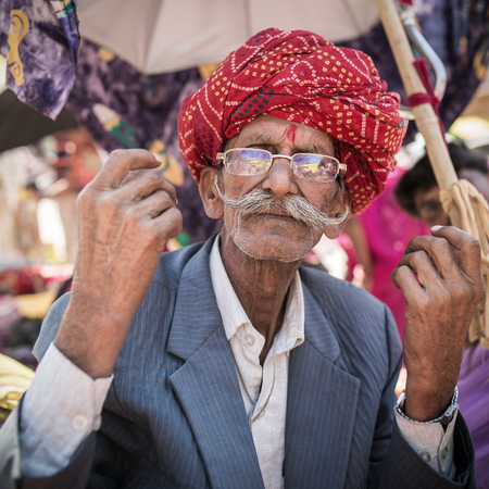 rajasthani: Jodhpur, India - March 9, 2016: Portrait of an unidentified rajasthani man with beautiful red turban and long mustaches