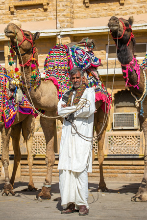 thar: Jaisalmer, India - March 3, 2016: Unidentified rajasthani man with camels waiting for tourists in Jaisalmer, India.