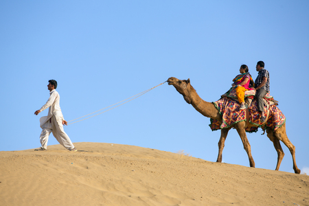 thar: Jaisalmer, India - March 13, 2016: Indian tourists on the camel in Thar desert, Rajasthan, India