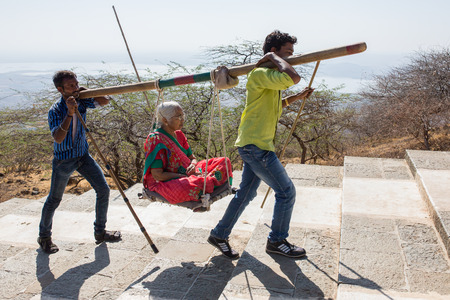 jainism: Palitana, India - March 6, 2016: Unidentified workers, carry pilgrims to the Jain temples on top of Mount Satrunjaya near Palitana, Gujarat, India. Editorial