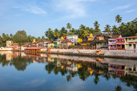 karnataka: Colorful indian houses on the bank of sacred lake Koti Teertha in Gokarna, India. Stock Photo
