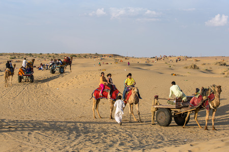 thar: Jaisalmer, India - March 13, 2016: Indian tourists  riding camels in Thar desert, Rajasthan, India
