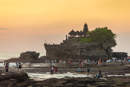 golde: Bali, Indonesia - July 23, 2016: Tourists walk near the Tanah Lot temple during sunset in Bali, Indonesia
