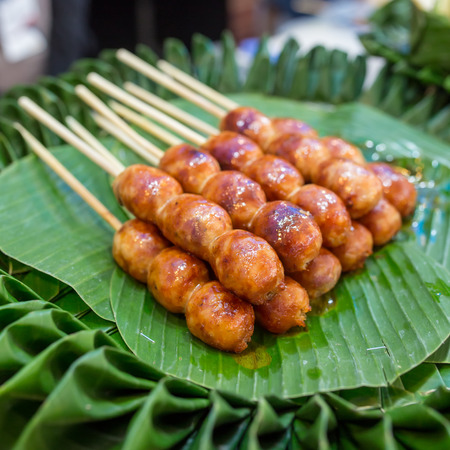 Traditional Thai style grilled Sausages on the banana leaf. Isaan pork meat sausage. Stock Photo