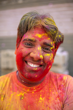 Barsana, India - March 17, 2016: Portrait of an unidentified man with face smeared with colors during Holi celebration in Barsana, Uttar Pradesh, India.