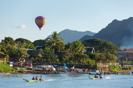 Vang Vieng, Laos - January 19, 2017: Unidentified tourists are riding  speedboats in Vang Vieng village with a hot air balloon on background. Editorial