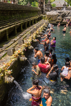Bali, Indonesia - August 7, 2016: Balinese Hindu families come to the sacred springs of Tirta Empul in Bali, Indonesia to pray.