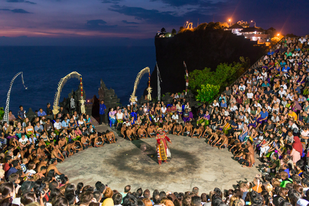 Bali, Indonesia - September 19: Tourists watch traditional Balinese Kecak Dance at Uluwatu Temple on Bali, Indonesia. Kecak (also known as Ramayana Monkey Chant) is very popular cultural show on Bali. Editorial