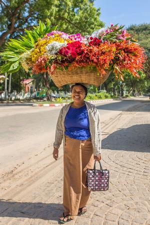 Bagan, Myanmar - October 12, 2016: Unidentified burmese woman carrying big basket of flowers on streets of Bagan, Myanmar.