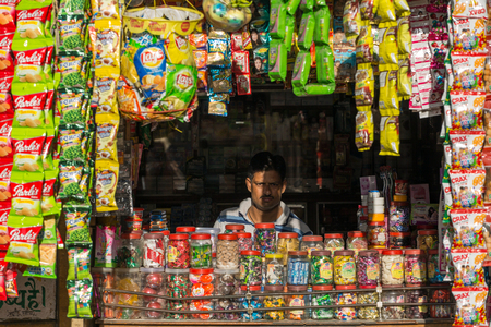 Jaisalmer, India - March 3, 2016: Unidentified indian vendor looking from  his street shop in Jaisalmer, India Редакционное