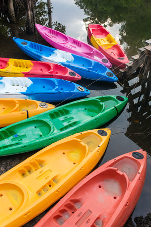 Group of colorful fiberglass kayaks on water in Thailand
