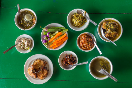Top view at the table with assorted burmese food in local restaurant in Myanmar. Stock Photo