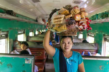 Mandalay, Myanmar - October 4, 2016: Unidentified burmese woman selling snaсks in the train between Mandalay and Hsipaw in Myanmar