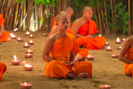 Chiang Mai, Thailand - November 14, 2016: Loy Kratong Festival, Buddhist monk fire candles to the Buddha and floating lamp on in Phan Tao Temple, Chiangmai, Thailand.