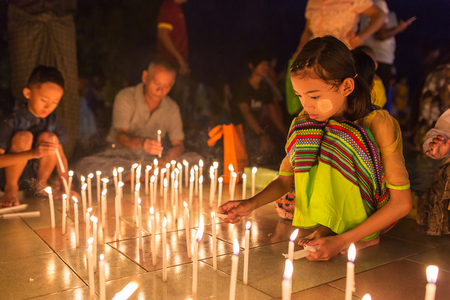 Mawlamyine, Myanmar - October 16, 2016: Unidentified burmese girl fire candles in buddhist temple during Thadingyut or  Lighting Festival in Mawlamyine, Burma Editorial