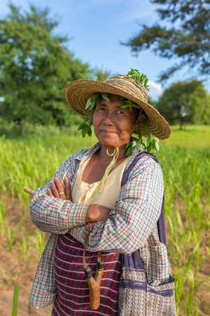 Bagan, Myanmar - Octobert 12, 2016: Portrait of an unidentified burmese farmer lady with a slingshot and anti mosquito leaves under the hat in Bagan, Myanmar