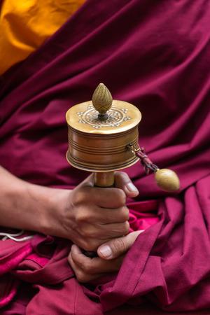 Tibetan prayer wheel in monks hands close-up Stock Photo