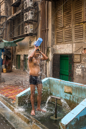 Mumbai, India - April 8, 2017: Indian man taking shower from bucket on streets of Mumbai, India Éditoriale