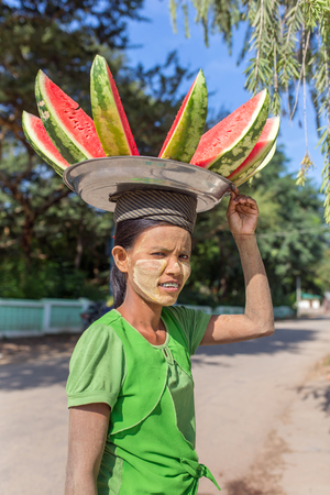 Bagan, Myanmar - October 13, 2016: Unidentified burmese woman carrying plate with watermelon on her head for sale on streets of Bagan, Myanmar. Editorial