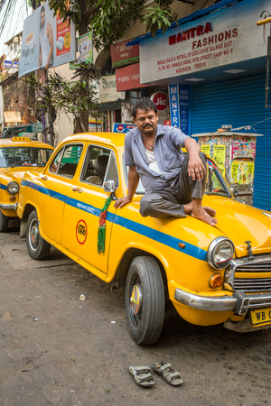 Kolkata, India - April 4, 2017: Portrait of an indian taxi driver with his antique oldtimer yellow taxi on the streets of Kolkata