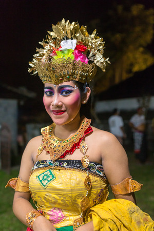 Ubud, Indonesia - August 29, 2016: Beautiful balinese woman dances during a traditional Kecak Fire Dance ceremony in Hindu temple.