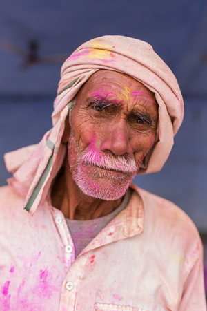 Nandgaon, India - March 18, 2016: Portrait of an unidentified man with face smeared with colors during Holi celebration in Nandgaon, Uttar Pradesh, India. Editorial
