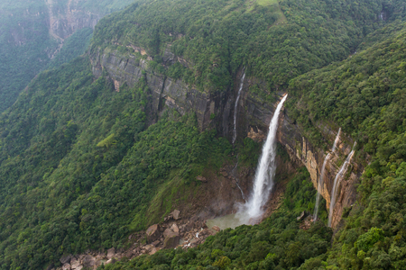 Nohkalikai waterfall surrounded by high cliffs and woodland and thick vegetation near Cherrapunji, Meghalaya, India.