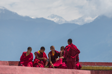 Sikkim, India - May 2, 2017: Tibetan monks rest at upper level of Rumtek Monastery near Gangtok with Himalayas mountains on background, Sikkim, India Editorial