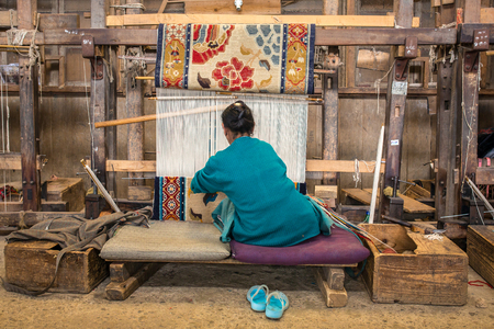 Darjeeling, India - April 19, 2017: Unidentified tibetan woman works as weaver in the carpet workshop of Tibetan Refugee Self Help Center, Darjeeling, India