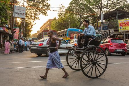 Kolkata, India - April 11, 2017: Traditional hand pulled indian rickshaw driver working on the street in Kolkata, West Bengal, India Editorial