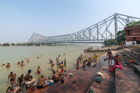 Kolkata, India - April 12, 2017: Unidentified indian people taking bath in Hooghly river with a Howrah bridge on background in Calcutta, West Bengal, India.