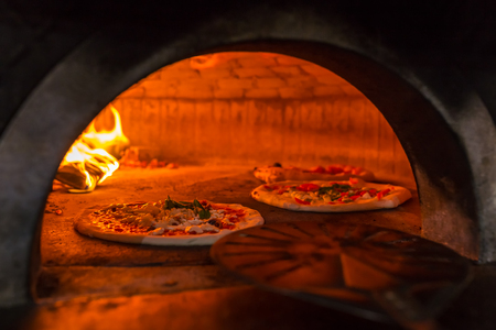 Original neapolitan pizza margherita in a traditional wood oven in Naples restaurant, Italy