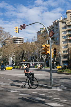 Barcelona, Spain - March 26, 2018: Unidentified man riding the penny-farthing, also known as a high wheel bicycle on the streets of Barcelona.