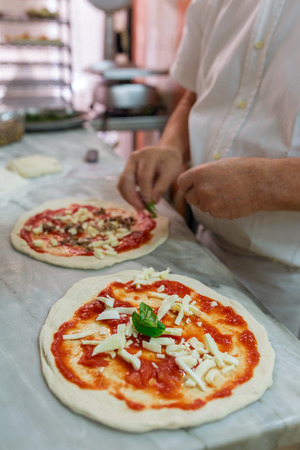 Preparing classic pizza Margherita in traditional pizzeria in Naples, Italy. Selective focus