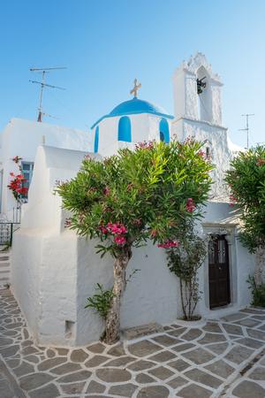 Cycladic greek orthodox church on Paros island, Greece. White cross against blue sea and sky