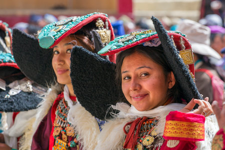 Lamayuru, India - June 19, 2017: Unidentified Zanskari women wearing ethnic costumes and traditional Ladakhi headdress with turquoise stones called Perakh Perak dancing during Buddhist festival in Lamayuru, Ladakh, India
