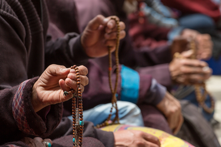 Buddhist beads in the hands of the tibetan pilgrims praying in Lamayuru monastery, Ladakh, India.