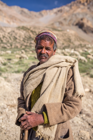 Sarchu, India - July 17, 2017: Portrait of unidentified indian shepherd with his sheeps near Sarchu camp in Ladakh, Northern India