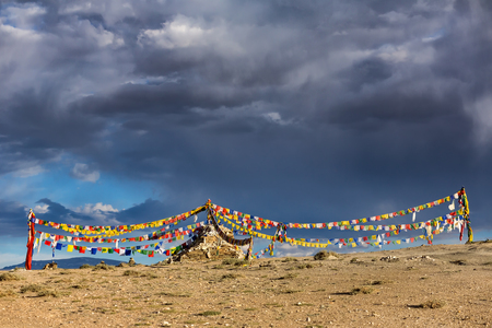 Old stone stupa with tibetan buddhist prayer flags in Ladakh, India.
