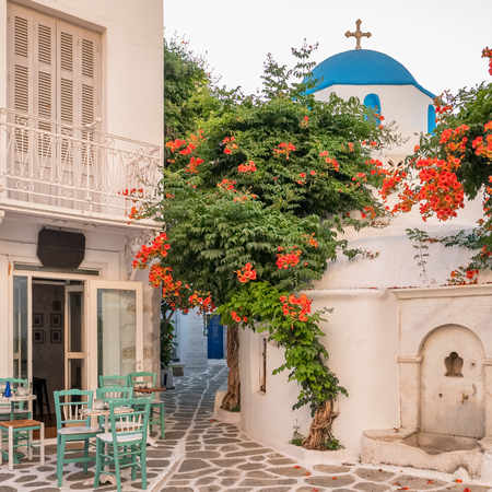 Cozy outdoor cafe and traditional greek church on the beautiful narrow street in Parikia town on Paros island cyclades Reklamní fotografie