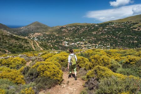 Woman with a backpack hiking on a hiking trail on Andros island, Greece