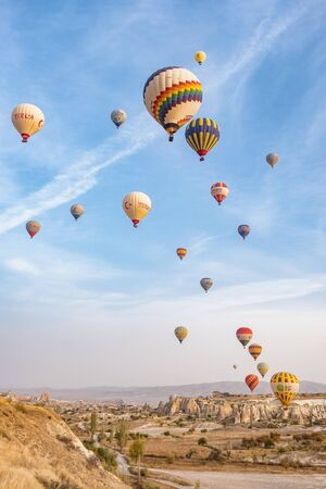 Hot air balloon flying over famous rock formations landscape of Cappadocia, Turkey