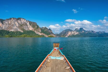 Wooden traditional thai longtail boat on Cheow Lan lake in Khao Sok National Park
