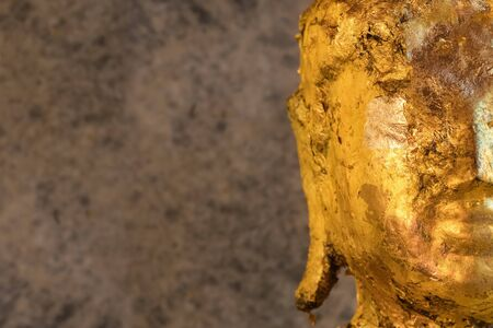 Buddha statue covered with golden papers close up.