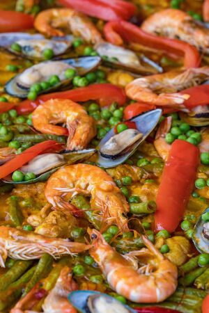 Spanish seafood paella in fry pan with mussels, shrimps and vegetables