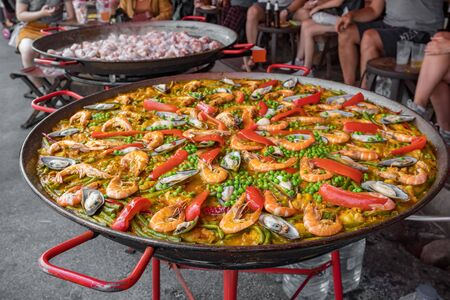 Big wok pan of spanish seafood paella with mussels, shrimps and vegetables